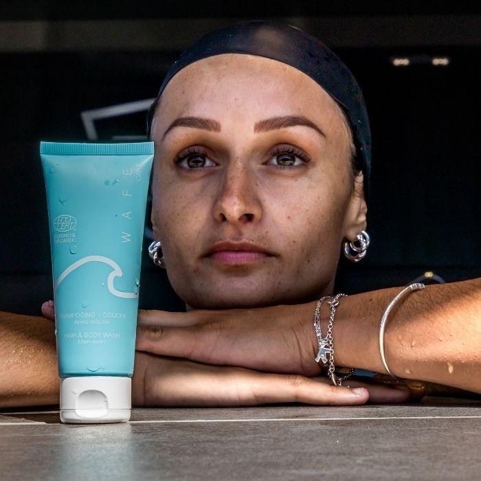 femme accoudée à une piscine avec un shampooing douche après piscine à côté d'elle