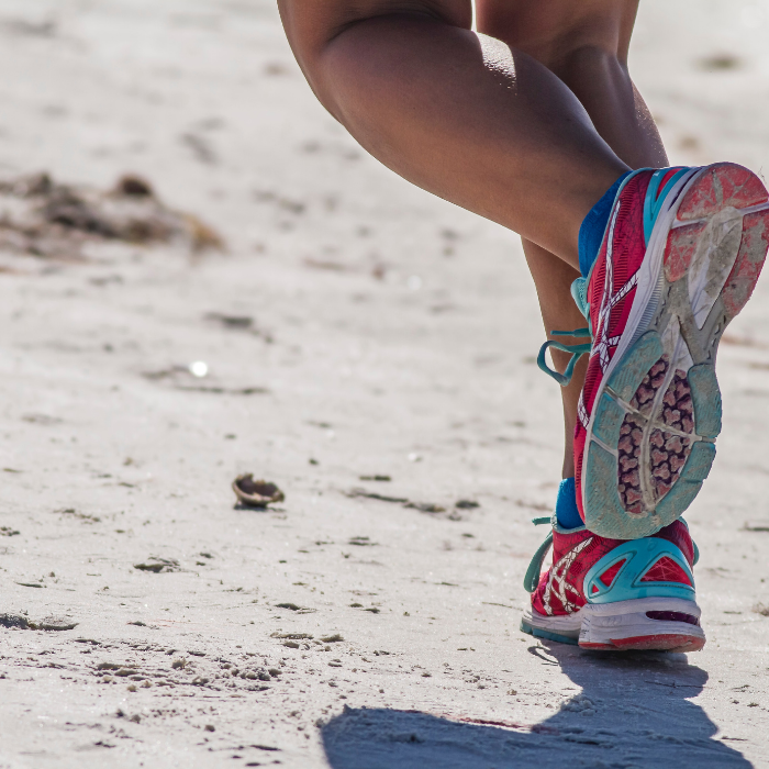 pieds avec chaussures de sport sur le sable