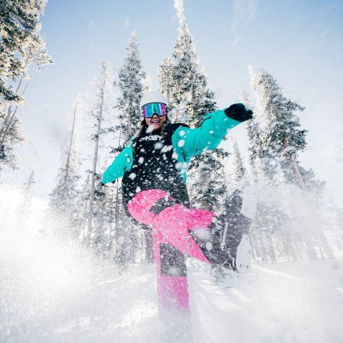 femme sous la neige qui fait du snowboard