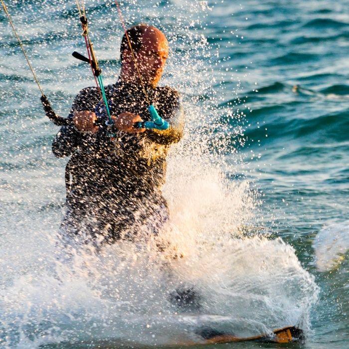 Homme qui fait du kite surf au soleil et en eau de mer