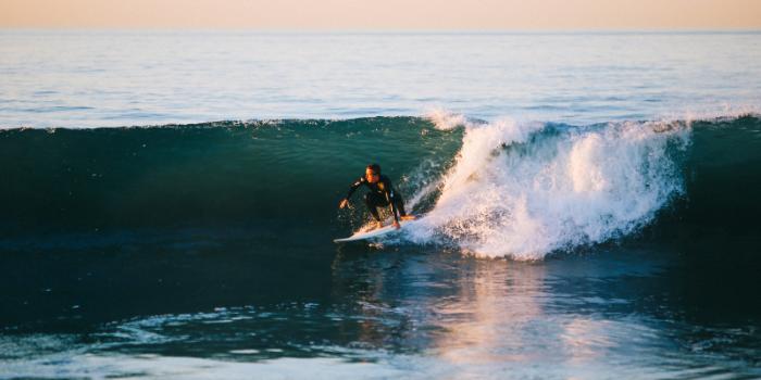 Homme faisant du surf en mer au soleil