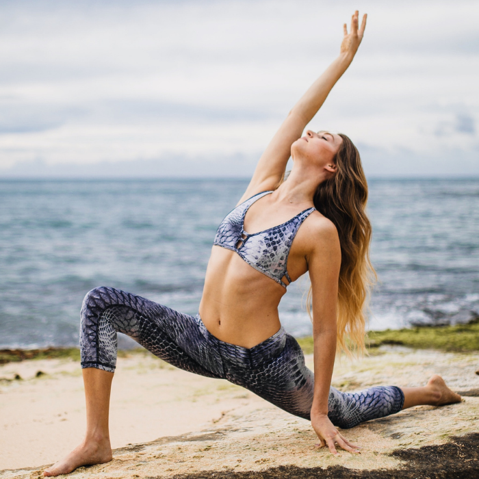 Femme qui fait du yoga au bord de l'eau