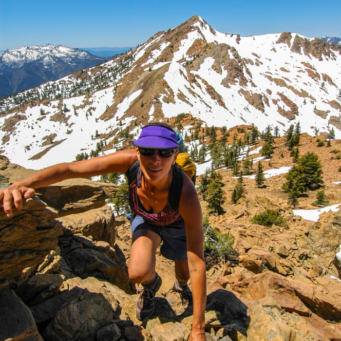 Femme qui fait de la randonnée et escalade dans la montagne