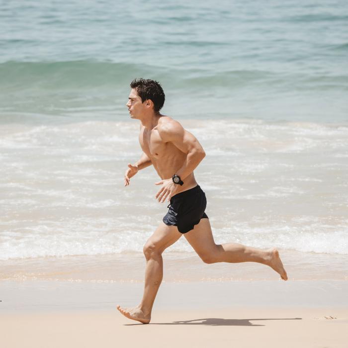 homme sportif qui fait un running sur la plage