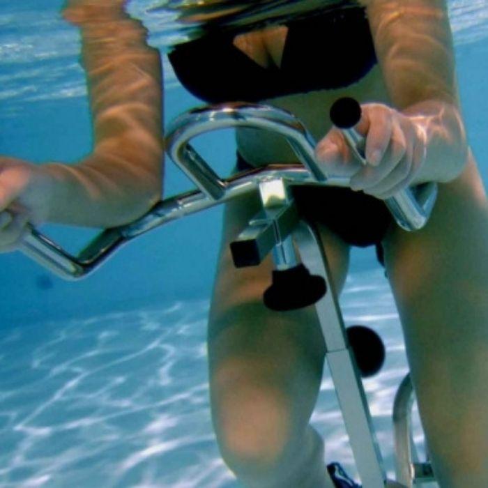 Femme sur un vélo d'aquabike dans une piscine