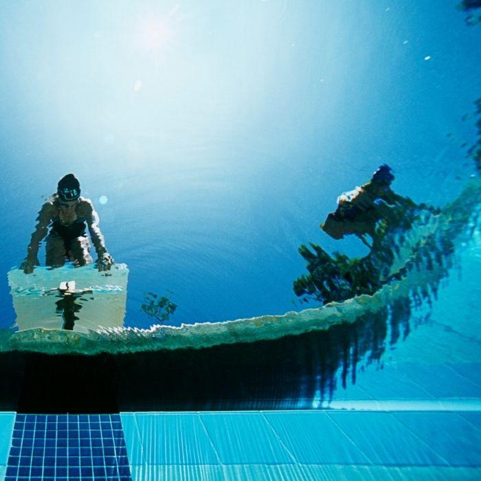 deux nageurs s'apprêtent à plonger dans une piscine